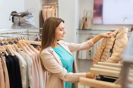 Verkauf, Einkaufen, Mode, Stil und Menschen Konzept - glückliche junge Frau, die Wahl Kleidung in der Mall oder Bekleidungsgeschäft