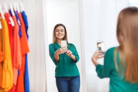 shirt hanger: clothing, fashion, style, technology and people concept - happy woman with smartphone taking mirror selfie at home wardrobe Stock Photo