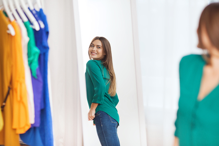 clothing, fashion, style and people concept - happy woman choosing clothes and posing at mirror at home wardrobe Stock Photo