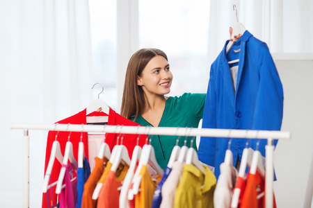 woman clothes: clothing, fashion, style and people concept - happy woman choosing clothes at home wardrobe