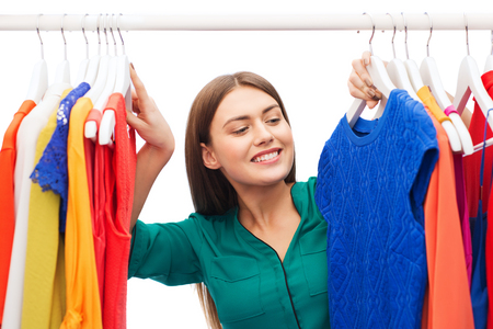 choosing clothes: clothing, fashion, style and people concept - happy woman choosing clothes at home wardrobe