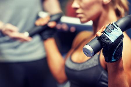 スポーツ、フィットネス、ボディービル、チームワークと人コンセプト - 若い女性やパーソナル トレーナーのジムのマシンで筋肉を屈曲