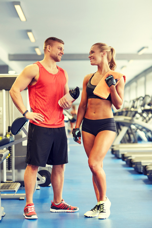 athletic wear: sport, fitness, lifestyle and people concept - smiling man and woman with protein shake bottle and towel talking in gym