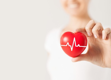 health, medicine, people and cardiology concept - close up of happy woman with cardiogram on small red heart
