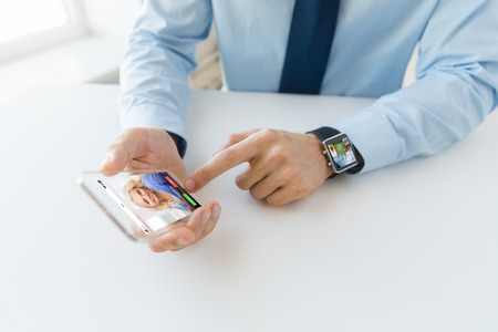 body parts cell phone: business, technology, communication and people concept - close up of male hand holding and showing transparent smart phone and watch at office with incoming call on screen
