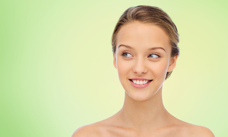 beauty, people and health concept - smiling young woman face and shoulders over green natural background
