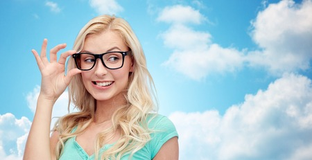 vision, education and people concept - happy smiling young woman or teenage girl glasses over blue sky and clouds background Stock Photo