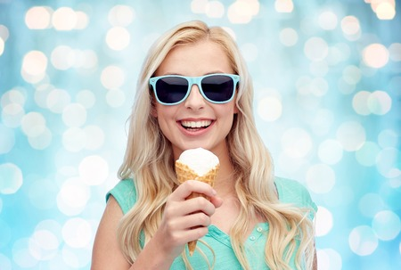 over eating: summer, junk food and people concept - young woman or teenage girl in sunglasses eating ice cream over blue holidays lights background