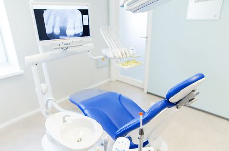 new medicine: dentistry, medicine, medical equipment and stomatology concept - interior of new modern dental clinic office with chair