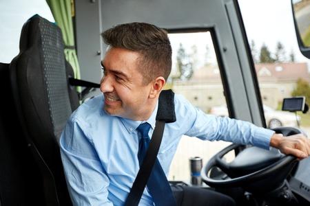 chofer de autobus: transporte, turismo, viaje por carretera y la gente concepto - controlador feliz conducción de autobuses interurbanos