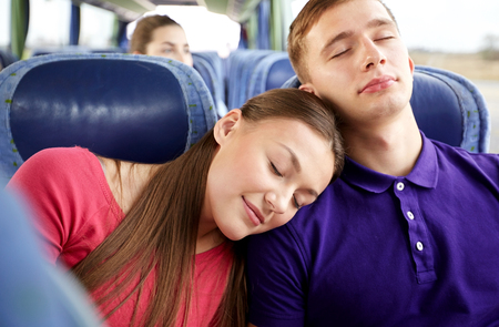 asleep: transport, tourism, road trip and people concept - happy teenage couple or tourists sleeping on shoulder in travel bus Stock Photo