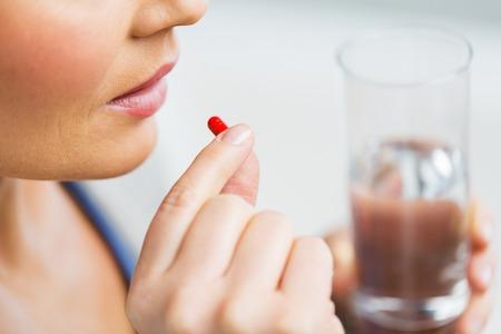 geneeskunde, gezondheidszorg en mensen concept - close-up van de vrouw die in de pil Stockfoto