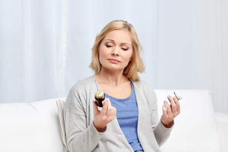 home health care: medicine, health care and people concept - woman looking at jars with medicine at home or hospital office
