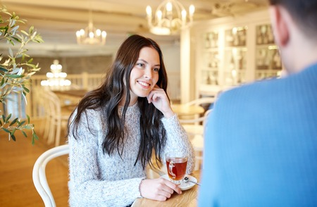 couple dating: people, communication and dating concept - happy couple drinking tea at cafe or restaurant