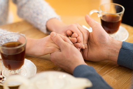holding close: people, love, romance and dating concept - close up of happy couple drinking tea and holding hands at cafe or restaurant Stock Photo