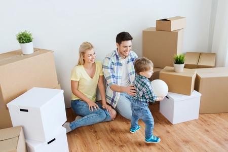 Hypothek, Menschen, Wohnen, Bewegen und Immobilien-Konzept - glückliche Familie mit Boxen Ball im neuen Zuhause spielen Standard-Bild - 60087571