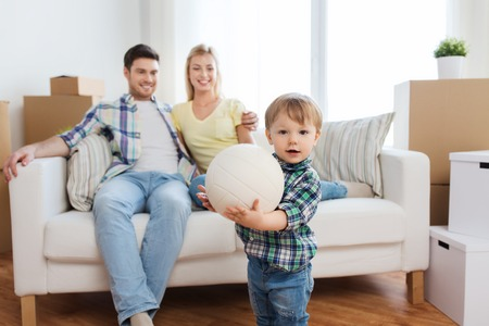 cardboard house: mortgage, people, housing, moving and real estate concept - happy little boy with ball over parents at home Stock Photo