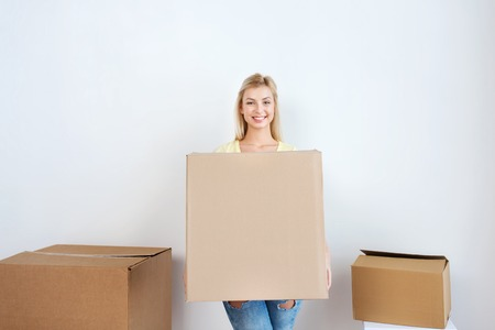 nice accommodations: moving, delivery, housing, accommodation and people concept - smiling young woman with cardboard box at home Stock Photo