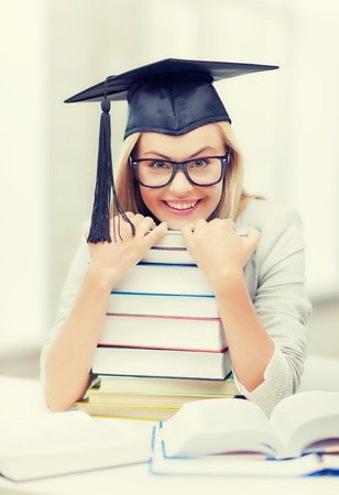picture of happy student in graduation cap with stack of books Stock Photo