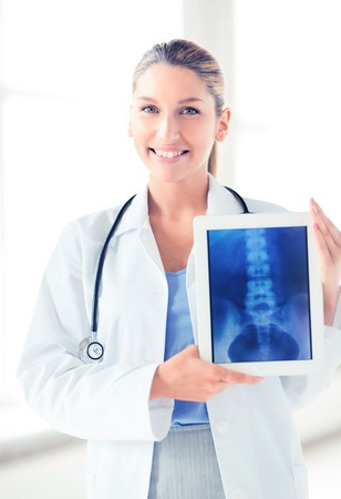 oncologist: bright picture of female doctor with x-ray on tablet pc Stock Photo