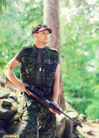 hunting, war, army and people concept - young soldier, ranger or hunter with gun in forest Stock Photo