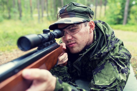 corps: hunting, war, army and people concept - close up of young soldier, ranger or hunter with gun in forest Stock Photo