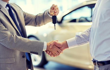 auto business, car sale, deal, gesture and people concept - close up of dealer giving key to new owner and shaking hands in auto show or salon Stockfoto