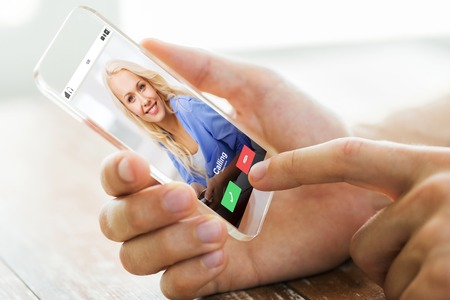 incoming: business, technology, communication and people concept - close up of male hand holding and showing transparent smartphone with incoming call from woman Stock Photo