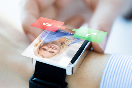 business, communication, technology and people concept - close up of woman hands setting smart watch with incoming call Stock Photo
