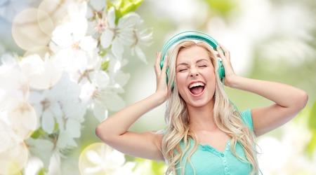 Musik, Technologie und Menschen Konzept - glückliche junge Frau oder Teenager-Mädchen mit Kopfhörer singen Lied über natürliche Frühling Kirschblüte Hintergrund Standard-Bild