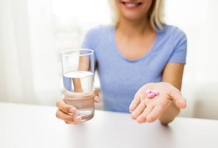 健康的な食事、医学、医療、食品、人々 の概念 - は、自宅の錠剤と水のガラスを保持している女性の手のクローズ アップ