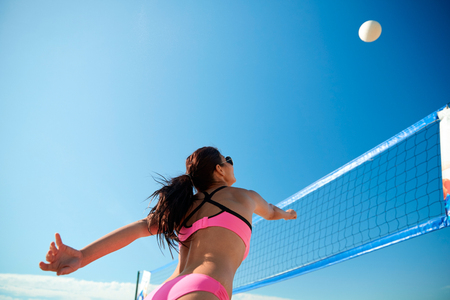 match: summer vacation, sport and people concept - young woman with ball playing volleyball on beach Stock Photo