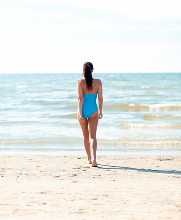 summer holidays: summer vacation, tourism, travel, holidays and people concept -young woman in swimsuit walking on beach from back