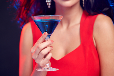 people, holidays, party, alcohol and leisure concept - close up of woman with cocktail at nightclub Stock Photo