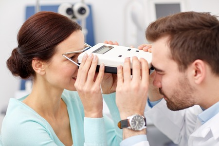 optician: health care, medicine, people, eyesight and technology concept - optometrist with pupilometer checking patient intraocular pressure at eye clinic or optics store
