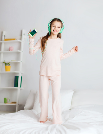 pajama party: people, children, pajama party and technology concept - happy smiling girl in headphones jumping on bed with smartphone and listening to music at home