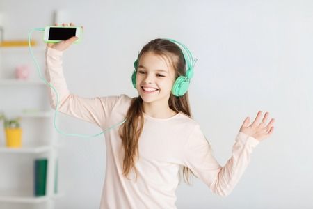girl home: people, children, pajama party and technology concept - happy smiling girl in headphones with smartphone and listening to music at home Stock Photo