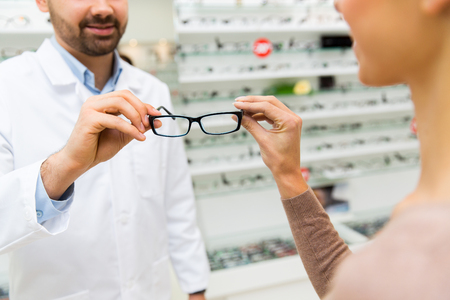 optician: health care, people, eyesight and vision concept - close up of optician showing glasses to woman at optics store