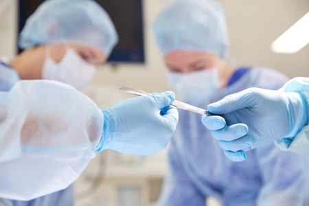 surgery, medicine and people concept - close up of surgeons hands with scalpel at operation in operating room at hospital