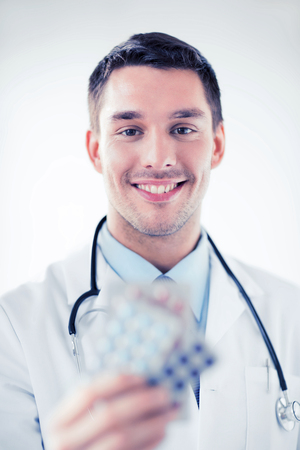 healthcare and medical concept - young male doctor with packs of pills