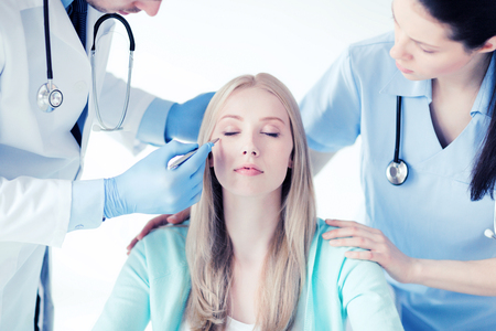 healthcare, medical and plastic surgery concept - plastic surgeon and nurse with patient in hospital