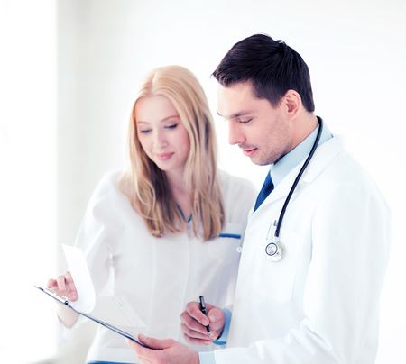 a lady doctor: healthcare and medical concept - two doctors writing prescription
