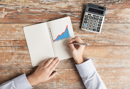 business, education, people and technology concept - close up of female hands with calculator, pen and chart drawing in notebook on table