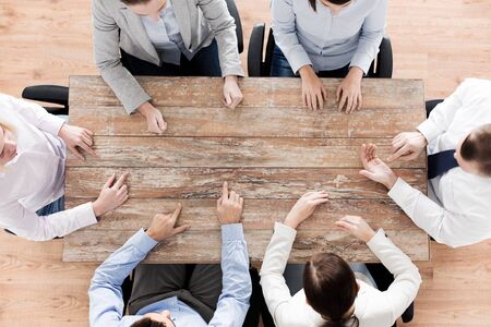 team communication: business, people and team work concept - close up of creative team sitting at table and pointing finger to something in office