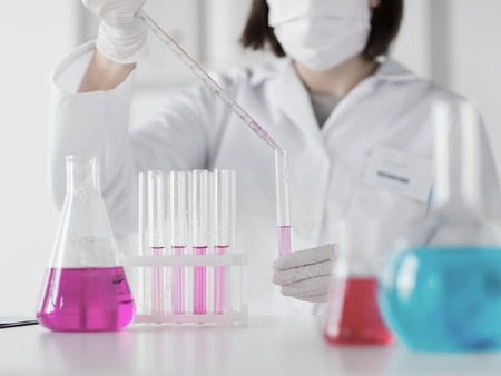 science, chemistry, biology, medicine and people concept - close up of young female scientist with pipette and flask making test or research in clinical laboratory Stock Photo