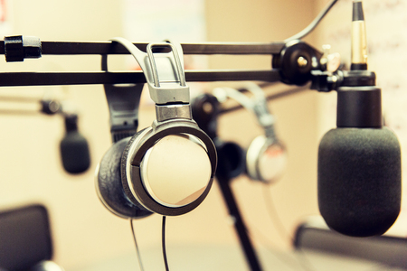 transmitting device: technology, electronics and audio equipment concept - close up of headphones and microphone at recording studio or radio station