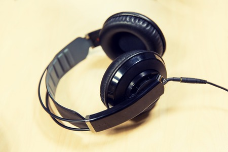 transmitting device: technology, electronics and audio equipment concept - close up of headphones at recording studio or radio station
