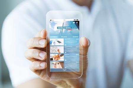 business, technologie en mensen concept - close-up van mannelijke hand houden en weer transparant smartphone met wereldnieuws webpagina op het scherm Stockfoto