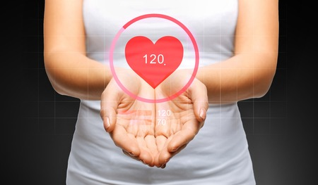 people, technology, health care, monitoring and cardiology concept - close up of womans cupped hands showing heart beat icon Stock Photo