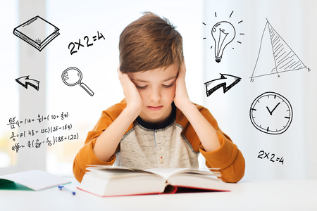 bored student: education, childhood, people, homework and school concept - bored student boy reading book or textbook at home over mathematical doodles